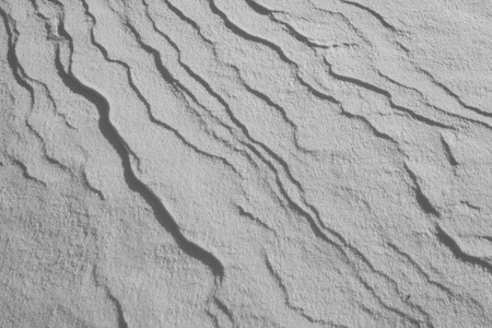 Wind drives and packs the snow leaving ripples, and shadows. Stock Photo