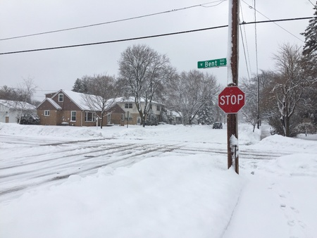 A winter storm leave a street intersection snow covered and slippery.