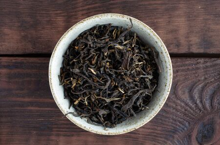Chinese red tea in bowl on wooden background. Gushu Dianhong.