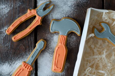 Ginger biscuit tools and icing sugar on wooden background. Top view. Ginger cookies.