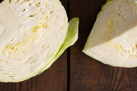 Cut cabbage on wooden background. Top view.