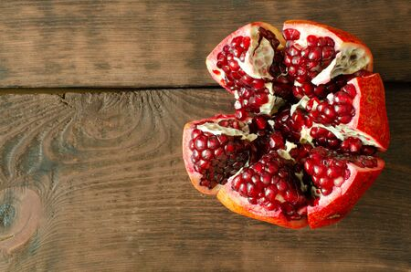 Opened pomegranate on wooden background with copy space. Top view