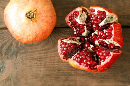 Pomegranate and opened pomegranate on wooden background with copy space. Top view 스톡 콘텐츠