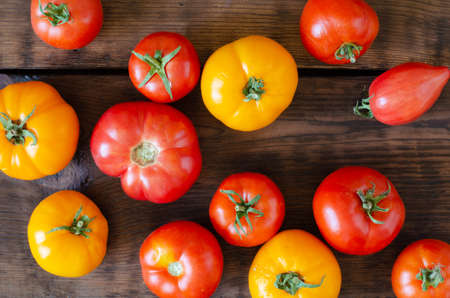 Yellow and red tomatoes on wooden background. Top view. Stock Photo