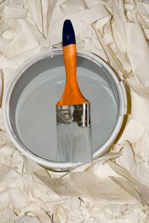 paintbucket:  Paint bucket and paintbrush over used wall paper