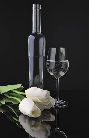 Glass and bottle of vine with flowers over black photo