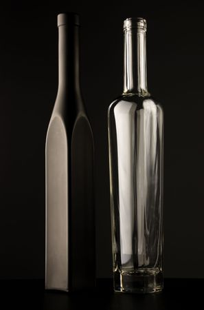 Empty black and transparent glass bottles over dark background photo