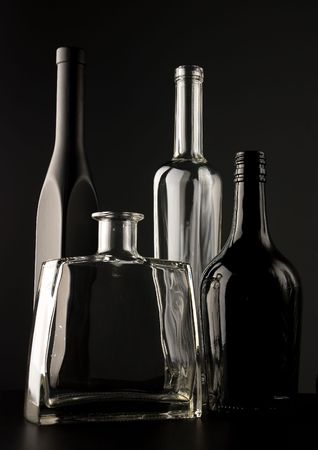 Empty black and transparent glass bottles over dark background photo