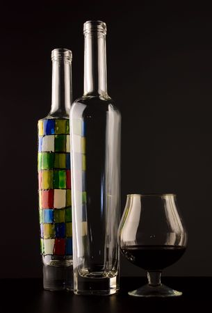 Empty bottles and glass of brandy over dark background photo