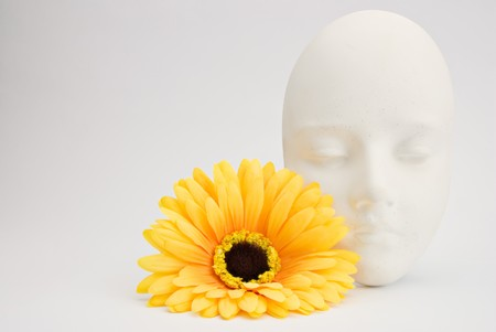 White clay mask and yellow artificial silk flower photo