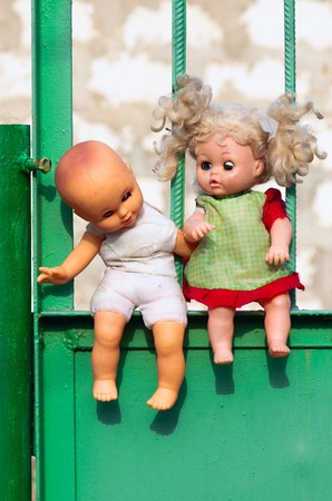 Concept: Abandoned Children. Old dolls sitting at fence photo