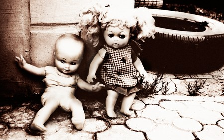 Concept: Abandoned Person. Close up of an old dolls at street. Special grunge-fashioned image with grain photo