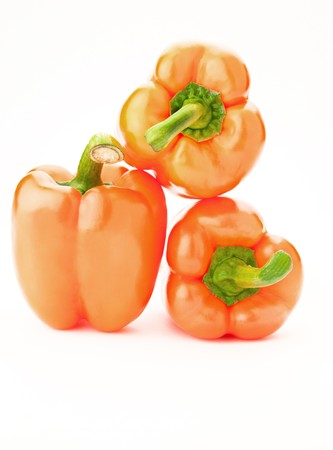 three orange peppers over white photo