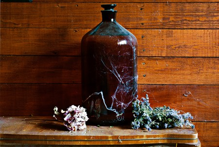 Old dusty barrel covered with cobweb and dry flowers in old village house photo