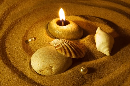 serenity: Summer evening background. Candle, seashells, stone and pearls on sand. Gold tinted image