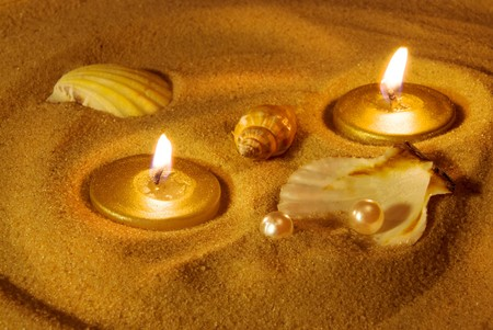 Summer evening background. Candles, seashells and pearls on sand. Gold tinted image photo