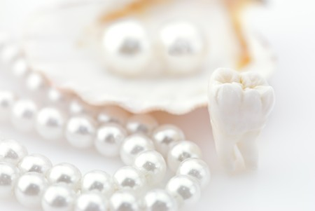 Healthy teeth concept. Real human wisdom tooth and natural pearls in an oyster shell. SHDOF pink colord image photo