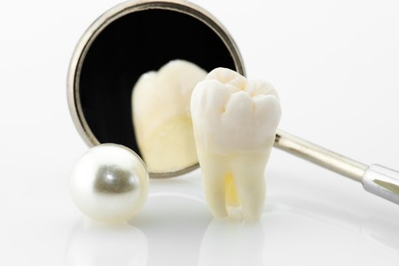 Healthy teeth concept. Real human wisdom tooth, natural pearl and dental mirror.  photo