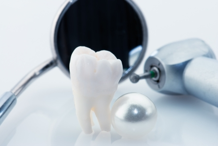 dental image: Healthy teeth concept. Real human wisdom tooth, natural pearl and dental tools. Blue tinted image