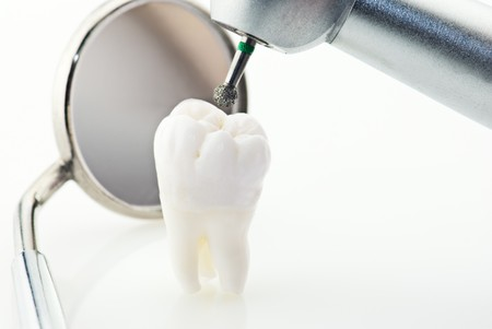 Healthy teeth concept. Real human wisdom tooth dental mirror and machine with drill