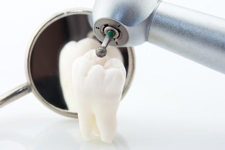 Concepto de dientes sanos. Espejo dental de diente de sabiduría humana real y la máquina con taladro