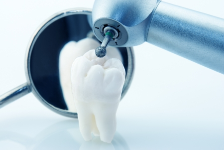 machine teeth: Healthy teeth concept. Real human wisdom tooth dental mirror and machine with drill. Blue tinted image