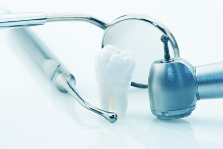 Healthy teeth concept. Real human wisdom tooth and dental tools. Blue tinted image photo