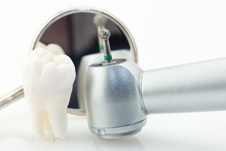 Healthy teeth concept. Real human wisdom tooth dental mirror and machine with drill photo