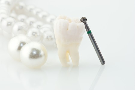 Healthy teeth concept. Real human wisdom tooth natural pearls and dental drill. photo
