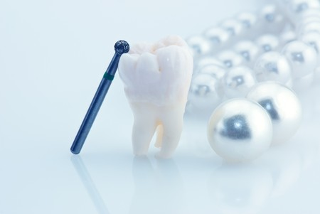 Healthy teeth concept. Real human wisdom tooth natural pearls and dental drill. Blue tinted image photo