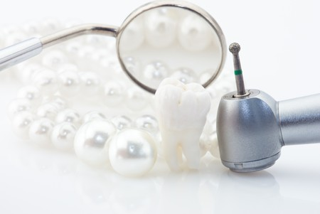 implant: Healthy teeth concept. Real human wisdom tooth natural pearls dental mirror and drill.