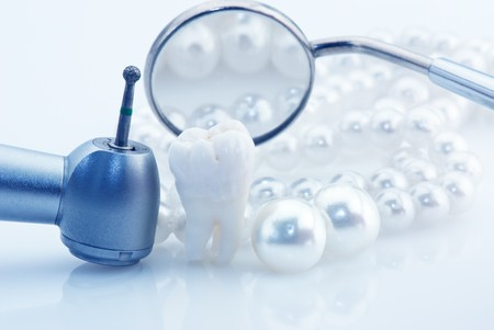 orthodontic: Healthy teeth concept. Real human wisdom tooth natural pearls dental mirror and drill. Blue tinted image