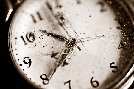 Broken time concept. Old dusty pocket clock with broken glass. Shallow depth of field. Sepia tinted image