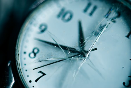 dusty: Broken time concept. Old dusty pocket clock with broken glass. Shallow depth of field. Blue tinted image Stock Photo