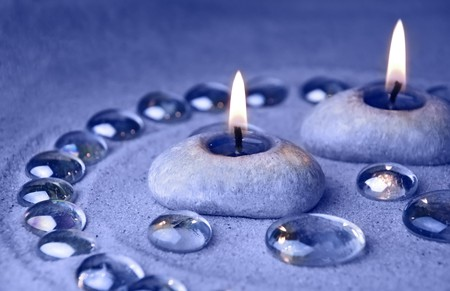 aromatherapy candle: Decoration background. Candles and glass drops on sand. Blue tinted image  Stock Photo