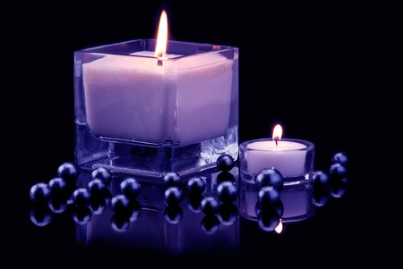 Decoration with burning candle and black pearls. Blue tinted image photo