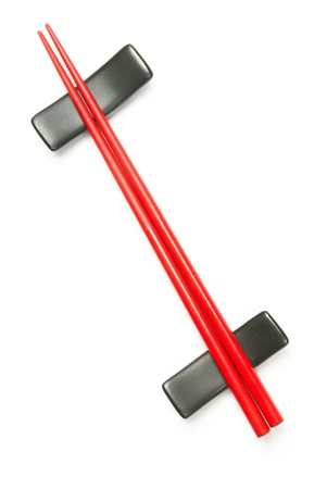 Two red wodden chopstick on holder over white Stock Photo - 8272823
