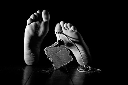 Death concept. Feet of a corpse on a wooden floor wearing a cardboard tag on rope. Black and white image with grain adding photo