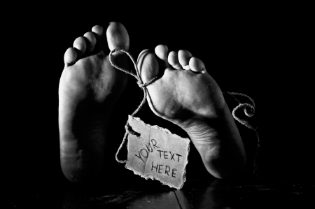 symbol victim: Death concept. Feet of a corpse on a wooden floor with cardboard tag on rope and handwritten text. Grunge processing, black&white image with grain added