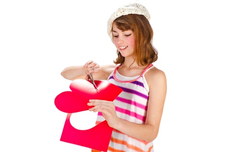 Cute girl in cap cutting valentine heart out of red paper with scissors photo