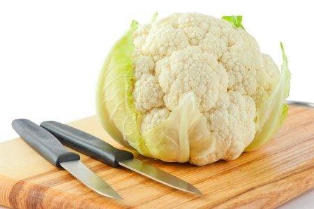 Cauliflower cabbage and two knives on wooden cutting board isolated on white background photo
