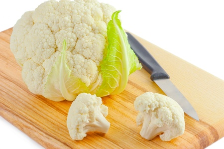 Cauliflower cabbage and  knife on wooden cutting board isolated on white background photo