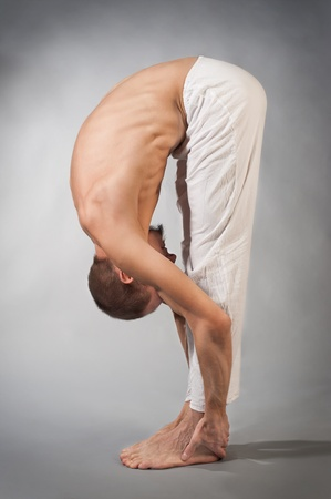 Handsome young man in yoga position. Studio portrait over gray background
