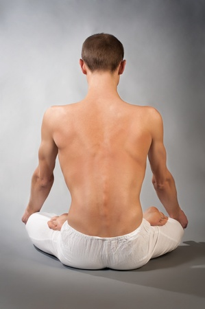 Back of young man in yoga position. Studio portrait over gray background photo