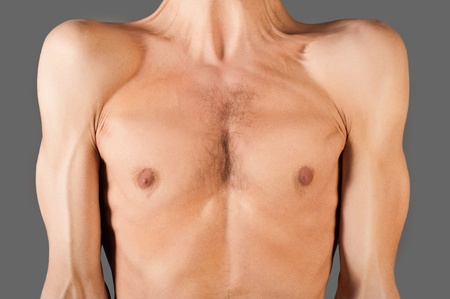 Part of skinny male torso. Isolated on gray.  photo