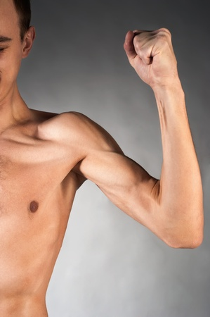 body built: Part of male torso and arm. On grey background Stock Photo
