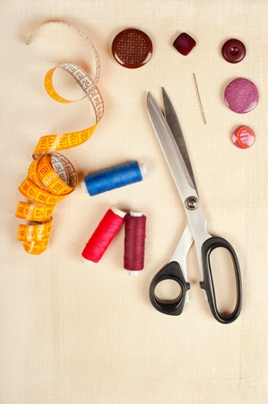 Sewing supplies. Set from measuring tape, buttons, bobbins of thread, needle and scissors on linen photo