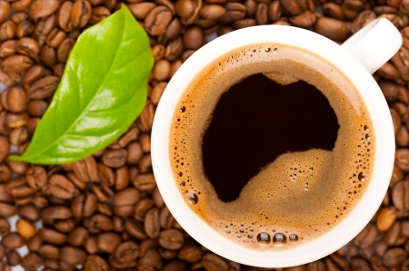 flavoured: Cup of coffee and coffee beans with green leaf of coffee plant. Focus on cup Stock Photo