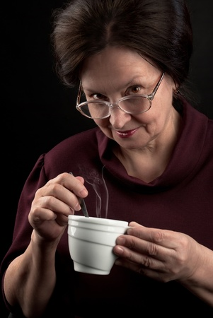 Smiling woman in glasses holding cup of hot drink. Studio portrait on dark background photo