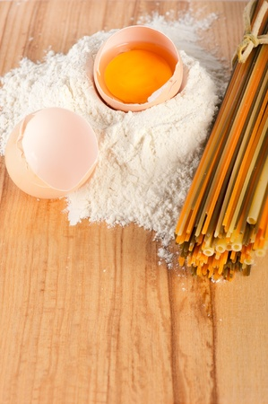 Flour with raw eggs and colored  spaghetti on wooden background Stock Photo - 9055401